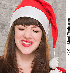 closeup of an upset christmas woman against a grunge wall