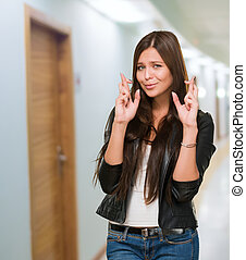 Young Woman With Crossed Fingers in a passage way
