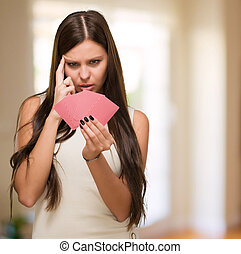 Confused Young Woman Holding Playing Cards