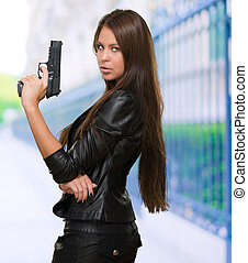 Portrait Of A Woman Holding Gun against a street background