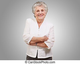 portrait of a adorable senior woman standing over grey...