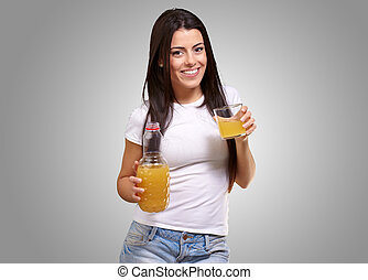 portrait of young girl drinking orange juice against a grey background