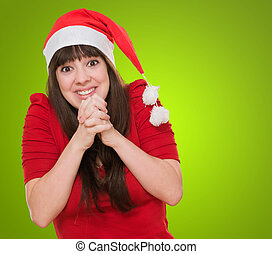 excited woman wearing a christmas hat against a green...