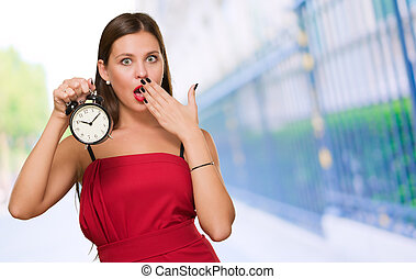 Shocked Woman Holding Alarm Clock against a street...