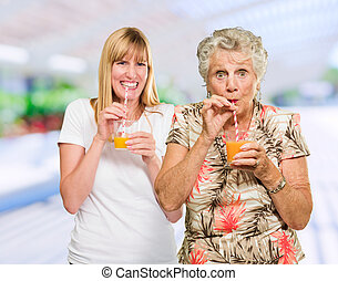 Two Happy Woman Drinking Juice, Outdoors