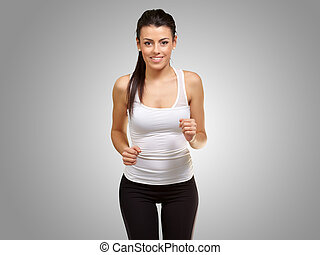 healthy young girl running over grey background