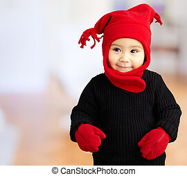 Portrait Of Baby Boy Wearing Warm Clothing against an...