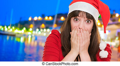 surprised christmas woman covering her mouth, outdoor