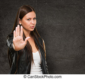 Young Woman Showing Stop Hand Gesture against a grunge...