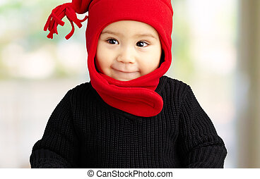 Portrait Of Baby Boy Wearing Warm Clothing at his home,...