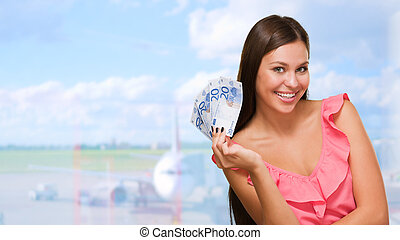 Happy Young Woman Holding Euro Currency at an airport