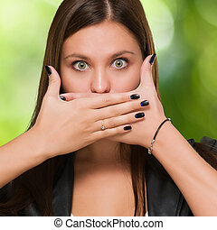 Shocked woman covering her mouth against a nature background