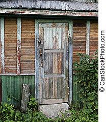 Old door of ramshackle house. - Old door of time-worn...