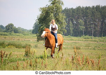 Beautiful blonde woman riding horse bareback and without...