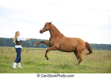 Young blonde woman commanding horse to rear stand up