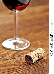 Cork and glass of italian red wine on a table in oak,...