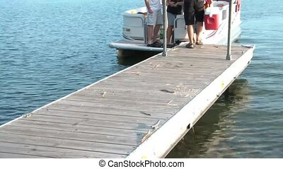 Boat Picking Up People at Dock - Pontoon boat picks up a...