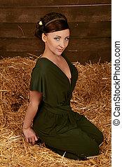 Beautiful Woman relaxing on wheat hay, studio shot