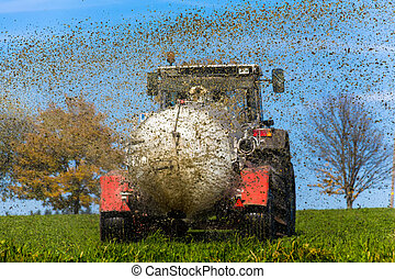 tractor fertilizes with manure a field - a tractor with...