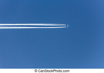 aircraft contrails - a plane with contrails in the blue sky....