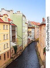 Colorful Prague houses near river under blue sky background
