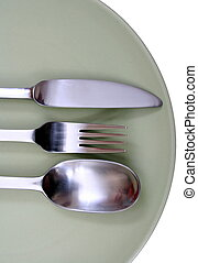 steel fork, spoon and knife on green plate