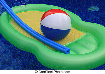 Inflatable toys in pool - Beach ball and floaty poised on...