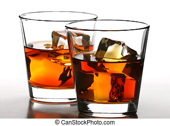 whiskey on rocks - glass of whiskey with ice cubes on white...