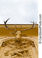Deer head on wall - A stone deer head with real antlers on a...
