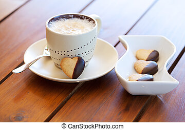Freshly baked heart-shaped cookie and cappuccino