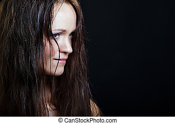 beautiful girl with long wet hair on a black background