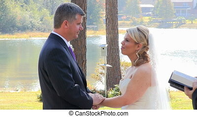 Wedding By Lake - Bride and groom exchange their wedding...
