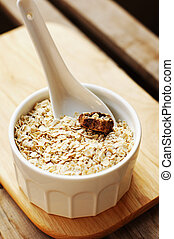 close up of wheat flakes in wooden spoon