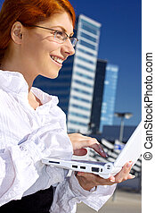 city life - happy businesswoman with laptop computer in the...