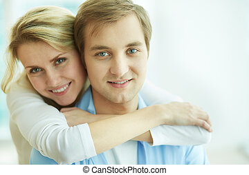 Togetherness - Image of young female embracing her husband...