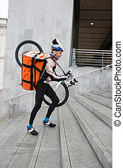 Male Cyclist With Courier Bag And Bicycle Walking Up Steps -...