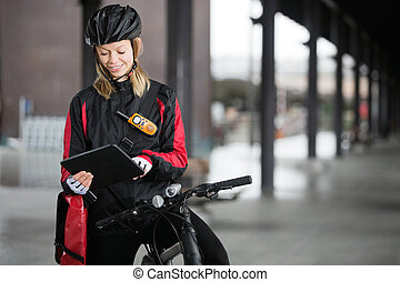 Female Cyclist With Courier Bag Using Digital Tablet