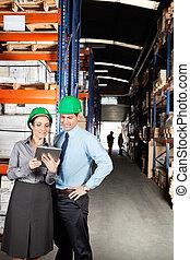 Supervisors Using Digital Tablet At Warehouse - Female...