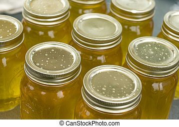 Natural Sweetener - Mason jars filled with clear sweet honey...
