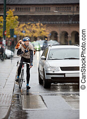 Male Cyclist With Backpack Using Walkie-Talkie On Street -...