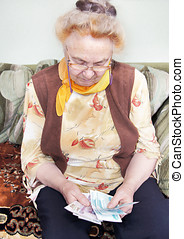 Elderly woman is counting the money