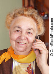 Elderly woman is talking by a mobile phone