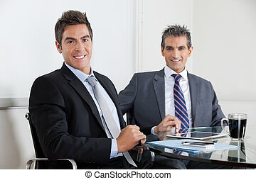 Businessmen Using Digital Tablet In Office