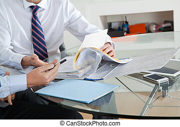 Businessman With Colleague Discussing Paperwork