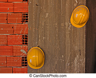 Construction workers yellow hard hats hanging on concrete...