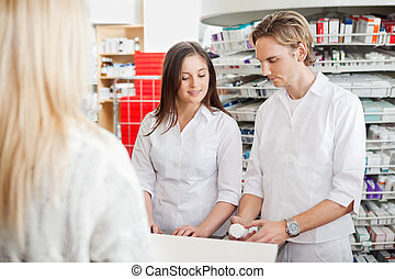 Pharmacy - Two young pharmacy works helping customer at...