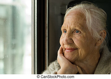 Lovely grandmother looking in a window, in a train