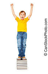 I won! - Cute boy standing on a pile of books and shouting