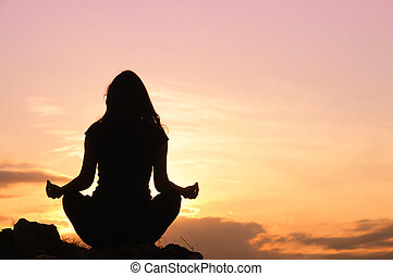 Woman meditation on the top of the - Silhouette of the...