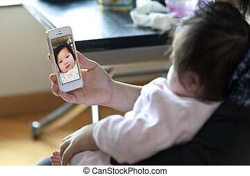 Mother takes photo by her phone for baby